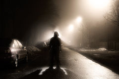 Ein Mann auf der nebeligen Straße nachts Stockbilder
