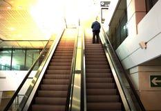 Ein Mann auf der Rolltreppe im Flughafen, Sonnenschein, sonniger Tag, hori stockfotografie