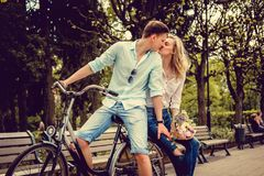 Ein Mann auf einem Fahrrad nette blonde Frau mit Blumen küssend Stockfoto