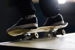 Ein Mann auf einem Skateboard tut einen Slippertrick auf einer Rampe lizenzfreies stockbild