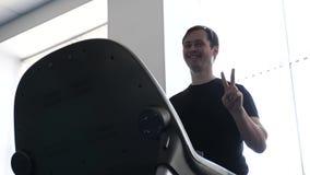 Ein Mann auf einer Tretmühle geht, Herz Last Fitness-Club-Mann teilgenommen an dem Gehen Verstärkung der Muskeln des Herzens und stock video