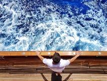 Ein Mann auf einer Yacht betrachtet das Meer stockfotos