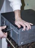 Ein Mann baut einen Computer mit einem Schraubenzieher in seinen Händen auseinander stockbild