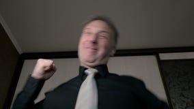 Ein Mann benutzt einen Smartphone, um zu arbeiten Erhält die guten Nachrichten Sehr viel gefiel Alles ist fein stock video