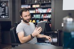 Ein Mann betrachtet die Tablette im Friseur ` s Stuhl in einem Mann ` s Friseursalon Stockbild