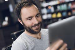 Ein Mann betrachtet die Tablette im Friseur ` s Stuhl in einem Mann ` s Friseursalon Stockfoto