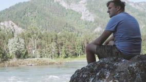 Ein Mann betrachtet einen Gebirgsfluss in Altai stock video
