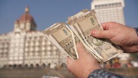 Ein Mann betrachtet indische 500 Rupien auf Mumbai-Straße H?nde schlie?en oben stock footage