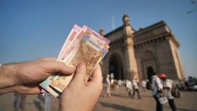 Ein Mann betrachtet indische Rupien vor dem hintergrund des Tors von Indien in der Stadt von Mumbai H?nde schlie?en oben stock footage