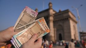 Ein Mann betrachtet indische Rupien vor dem hintergrund des Tors von Indien in der Stadt von Mumbai H?nde schlie?en oben stock video