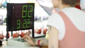 Ein Mann bildet mit Gewichten in der Turnhalle aus Der Lehrer regelt das Ergebnis stock video