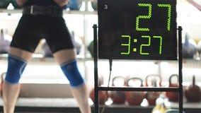 Ein Mann bildet mit Gewichten in der Turnhalle mit dem Reparieren der Ergebnisse aus stock video footage