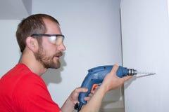 Ein Mann bohrt eine Wand mit einem Bohrgerät lizenzfreie stockbilder