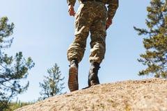 Ein Mann in den alten Schuhen der Tarnung mit Spitzen für das Klettern auf Felsen Trikoni Tricouni Lizenzfreies Stockbild