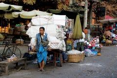 Ein Mann in den blauen Sarongen zieht einen großen Warenkorb Lizenzfreie Stockbilder