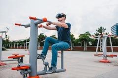 Ein Mann in den Gläsern der virtuellen Realität tut Sport Zukünftiges Technologiekonzept Moderne Bildgebungstechnologie Klassen h Lizenzfreie Stockfotos
