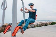 Ein Mann in den Gläsern der virtuellen Realität tut Sport Zukünftiges Technologiekonzept Moderne Bildgebungstechnologie Klassen h Stockfotografie