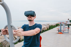 Ein Mann in den Gläsern der virtuellen Realität tut Sport Zukünftiges Technologiekonzept Moderne Bildgebungstechnologie Klassen h Lizenzfreies Stockbild