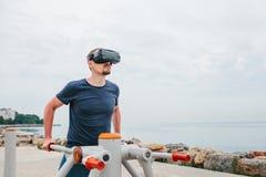 Ein Mann in den Gläsern der virtuellen Realität tut Sport Zukünftiges Technologiekonzept Moderne Bildgebungstechnologie Klassen h Stockfoto