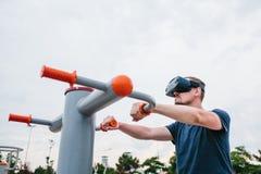 Ein Mann in den Gläsern der virtuellen Realität tut Sport Zukünftiges Technologiekonzept Moderne Bildgebungstechnologie Klassen h Stockbild