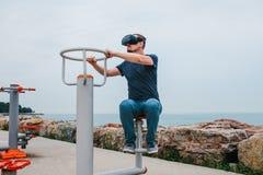 Ein Mann in den Gläsern der virtuellen Realität tut Sport Zukünftiges Technologiekonzept Moderne Bildgebungstechnologie Klassen h Lizenzfreie Stockfotografie