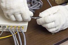 Ein Mann in den Handschuhen hält ein Netzkabel, ein Modem, ein Nahaufnahmemodem stockfotos