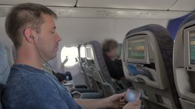 Ein Mann in den Kopfhörern ein Video, hörend Musik an seinem Handy aufpassend und im Flugzeug sitzen stock video