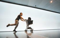 Ein Mann in den Sporthosen und eine Weste, die spät mit einer Laufkatze am Flughafen für einen Flug gegen eine weiße Fahne läuft Lizenzfreie Stockfotos