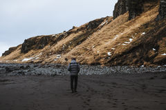 Ein Mann, der allein auf schwarzen Sandstrand mit Klippe geht Lizenzfreie Stockfotografie