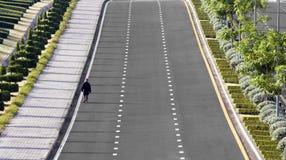 Ein Mann, der alleine entlang die Straße geht Lizenzfreies Stockfoto