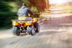 Ein Mann, der ATV auf eine Sandstraße, hintere Ansicht reitet stockfotografie