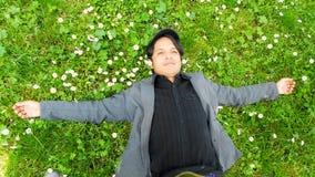 Ein Mann, der auf dem Gras liegt stockbilder