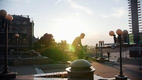 Ein Mann, der auf dem Stand und dem Sprung auf der Vorwölbung - Sonnenuntergang läuft stock footage