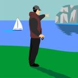 Ein Mann, der auf dem Strand mit einer Kamera steht Stockfotografie