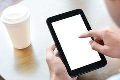 Ein Mann, der auf dem Tisch Tabletten-PC mit Kaffeetasse verwendet Stockbilder