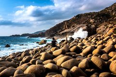 Ein Mann, der auf den Felsen, Fotos von Wellen an wilde Eggshaped Felsen nehmend sitzt, setzen mit drastischen Wolken im Himmel a lizenzfreies stockbild