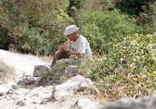 Ein Mann, der auf einem Rohr sitzt auf der touristischen Spur spielt krim Lizenzfreie Stockfotos