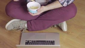 Ein Mann, der auf einem Schreibentext des Bretterbodens auf der Laptoptastatur sitzt und Nudeln mit Essstäbchen isst stock footage
