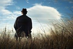 Ein Mann, der auf einem Stuhl in der Landschaft sitzt Lizenzfreie Stockbilder