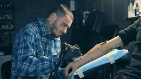 Ein Mann, der auf einer prothetischen Hand, bionische Ausrüstung tätowiert stock footage