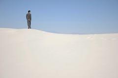 Ein Mann, der auf einer Sanddüne steht Stockbilder