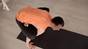 Ein Mann, der auf einer Yoga Matte sitzt und Übungen in einem speziellen Raum tut Das Konzept der Gesundheit und der St?rke stock video footage