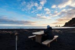 Ein Mann, der auf Holzbank am schwarzen Sand-Strand im Sonnenuntergang sitzt Stockfotos
