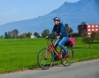 Ein Mann, der auf Landstra?e in der Luzerne radf?hrt lizenzfreies stockbild