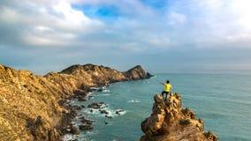 Ein Mann, der auf der Spitze des Berges durch Ozean steht stockfotografie