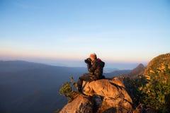 Ein Mann, der auf Stein und schießender Ansicht sitzt Stockbilder