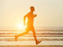 Ein Mann, der auf Strand mit Sonnenuntergang läuft Stockfotografie