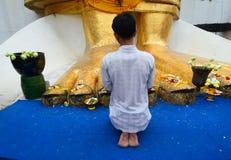 Ein Mann, der am buddhistischen Tempel in Bangkok, Thailand betet Stockfoto