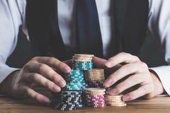 Ein Mann, der Chips auf einer Tabelle stapelt lizenzfreie stockfotos