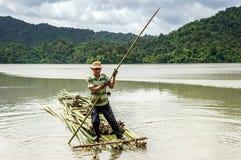Ein Mann, der das Bambusfloss auf dem See rudert Lizenzfreies Stockfoto